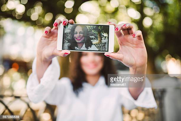 Young woman taking a selfie with her smartphone, close-up