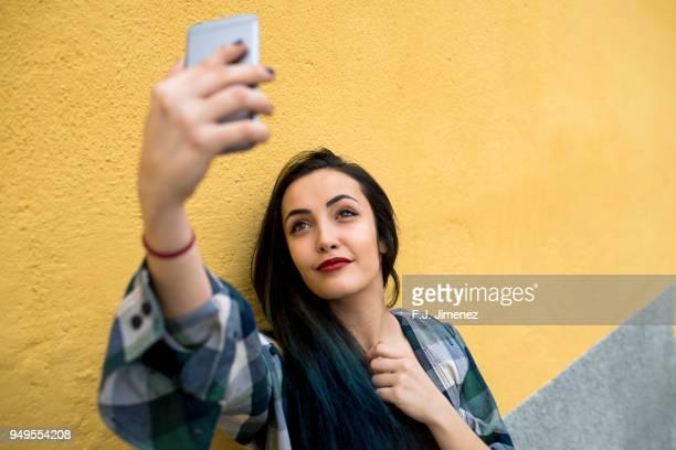 Young woman taking a selfie with smart phone in front of yellow wall