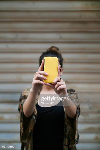 young woman taking a selfie with smartphone - obscured face stock pictures, royalty-free photos & images