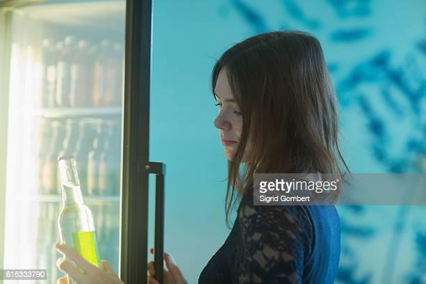young woman taking a soda bottle out of refrigerator, freiburg im breisgau, baden-württemberg, germany - sigrid gombert fotografías e imágenes de stock