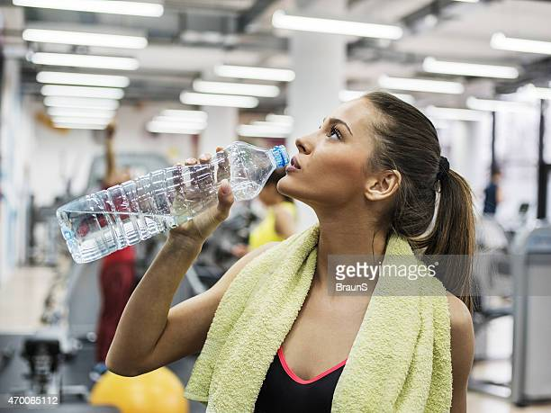 Young woman taking a water break in a health club.