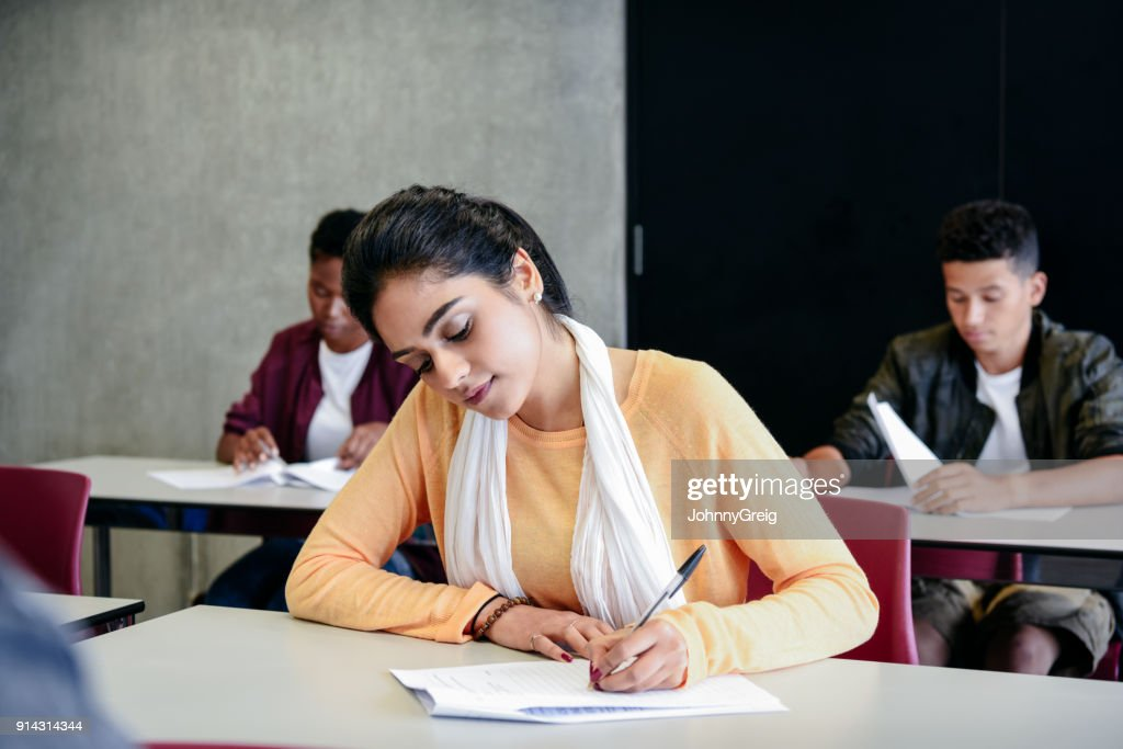 Young woman taking an exam writing at desk in classroom : Stock Photo
