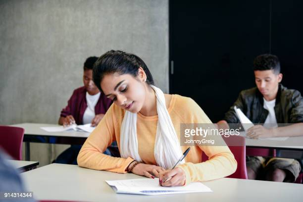 young woman taking an exam writing at desk in classroom - english stock photos and pictures
