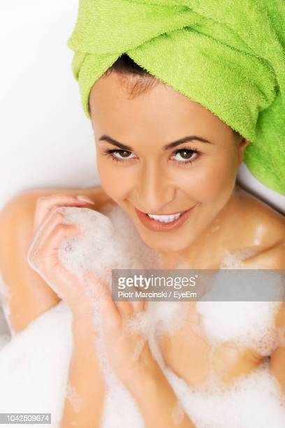 young woman taking bath in bathroom at home - loofah stock photos and pictures