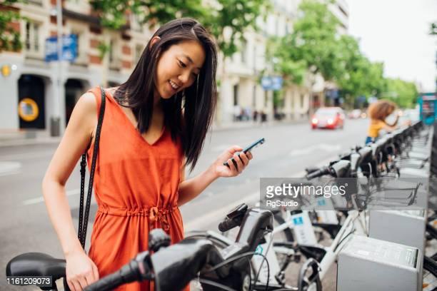 jonge vrouw die fiets neemt - onderweg stockfoto's en -beelden