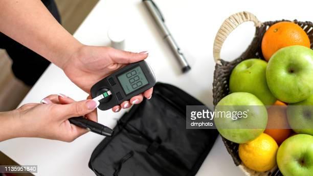 mujer joven tomando la prueba de azúcar en la sangre - diabetes fotografías e imágenes de stock