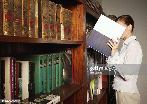 young woman taking book from bookshelf. - viso nascosto foto e immagini stock