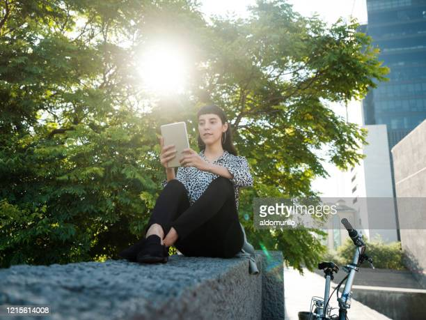 young woman taking break outside and using digital tablet - legs crossed at ankle stock pictures, royalty-free photos & images