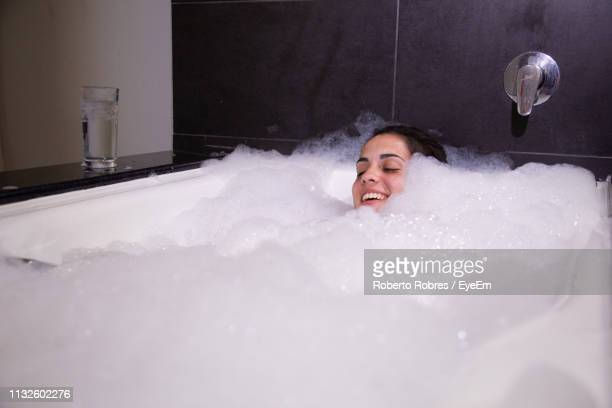 young woman taking bubble bath in bathtub - bubble bath stock pictures, royalty-free photos & images