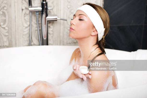 Young Woman Taking Bubble Bath In Bathtub
