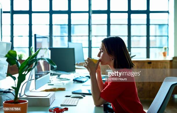 young woman taking coffee break at desk with eyes closed - 休憩中 ストックフォトと画像