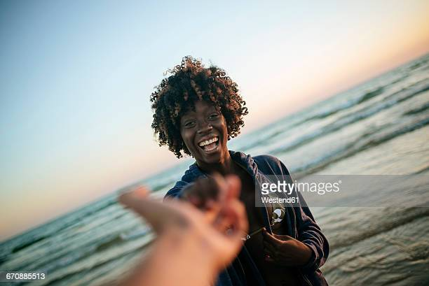 Young woman taking hand of a man on the beach at sunset