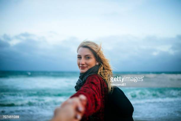Young woman taking hand of a man on the beach