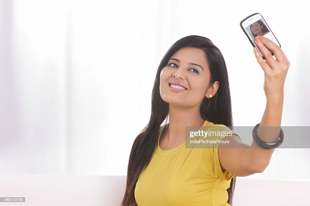 Young woman taking her own photograph : Stock Photo