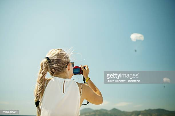Young woman taking images of two skydivers