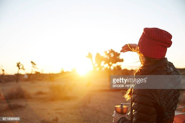 Young woman taking in sunrise at campsite