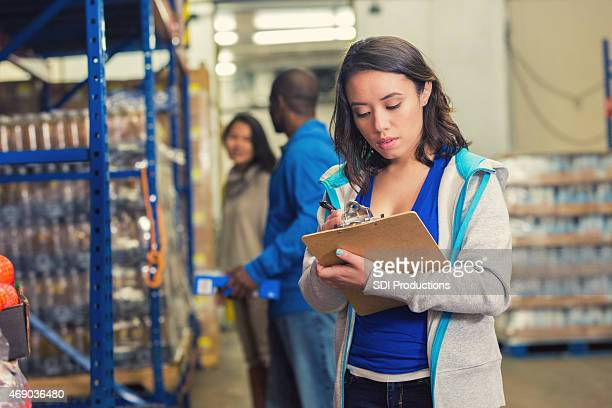 young woman taking inventory of donations in food bank warehouse. - humanitarian aid stock pictures, royalty-free photos & images