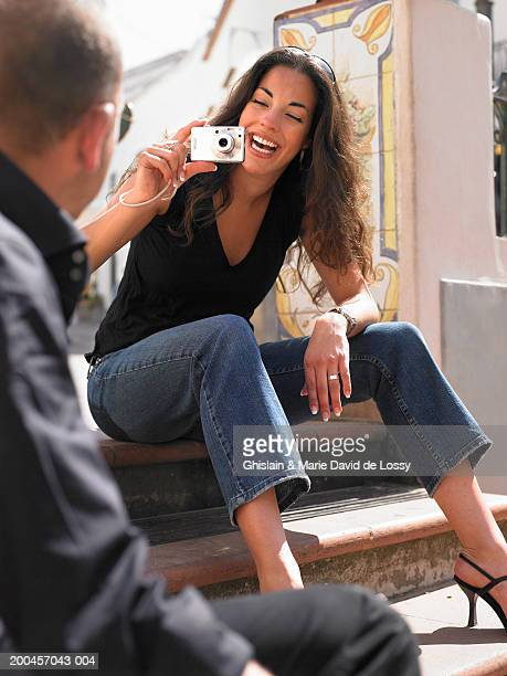 Young woman taking man's photo with digital camera