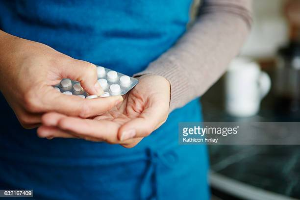 young woman taking medication from blister pack, close-up - blister pack stock pictures, royalty-free photos & images