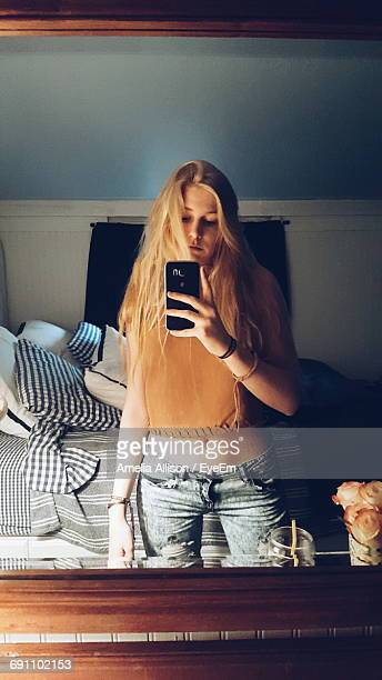 young woman taking mirror selfie at home - mirror selfie stock pictures, royalty-free photos & images