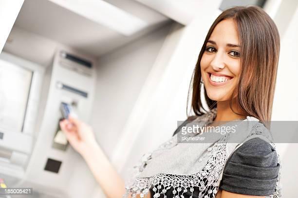 Jeune femme de prendre de l'argent dans un distributeur automatique de billets.