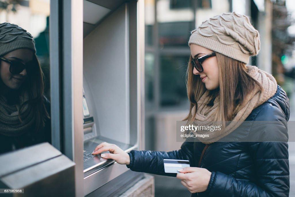Joven mujer tomando dinero de cajero automático : Foto de stock