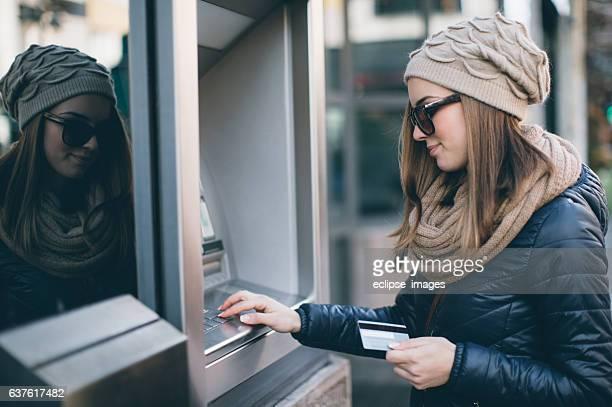 Jovem mulher com dinheiro no Caixa Automático