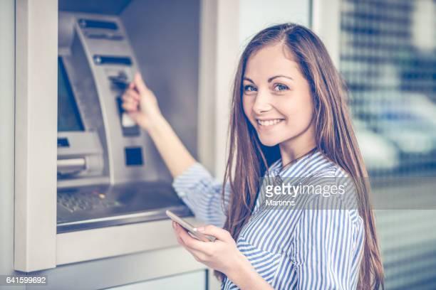 Junge Frau, die Geld von ATM