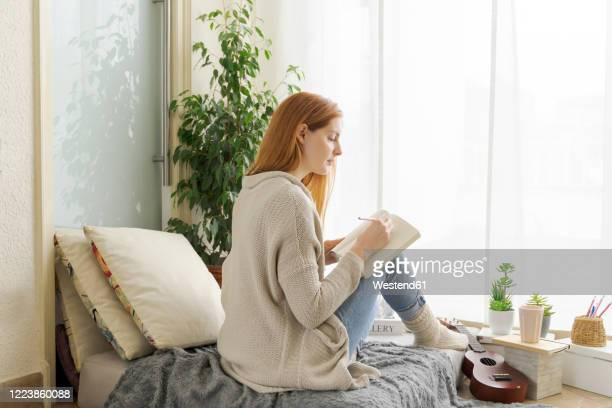 young woman taking notes at home - tagebuch stock-fotos und bilder