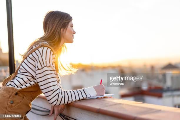 young woman taking notes on roof terrace at sunset - contemplação imagens e fotografias de stock