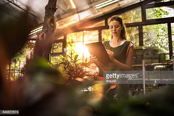 Young woman taking notes while working in a greenhouse.