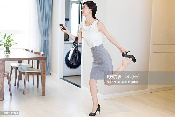 young woman taking off her high heels after work - standing on one leg stock pictures, royalty-free photos & images