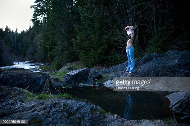 young woman taking off shirt , standing on rock near water - bikini top stock pictures, royalty-free photos & images