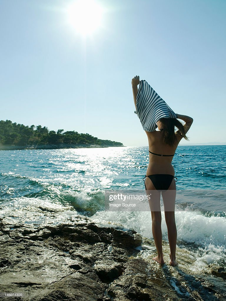 Young woman taking off t-shirt by the sea : Stock Photo