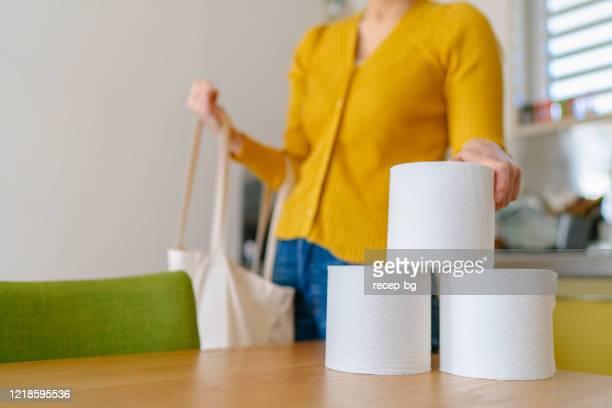 自宅で買い物袋からトイレットペーパーを取り出す若い女性 - トイレットペーパー ストックフォトと画像