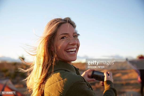 young woman taking photo at campsite - camping stock-fotos und bilder