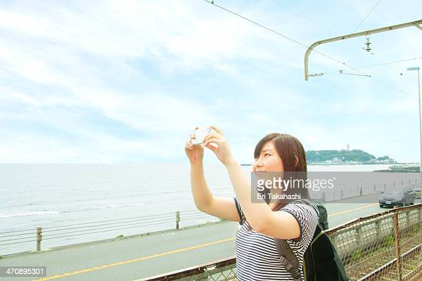 Young woman taking photo at coast with smartphone