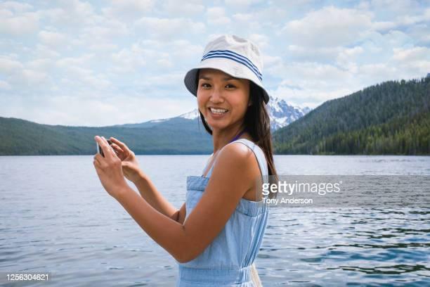 young woman taking photo at mountain lake - チューリップ帽 ストックフォトと画像
