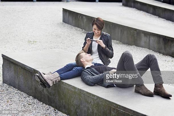young woman taking photo of boyfriend - coat foto e immagini stock