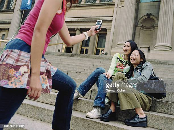 young woman taking photo of friends on museum steps, portrait - met art gallery ストックフォトと画像