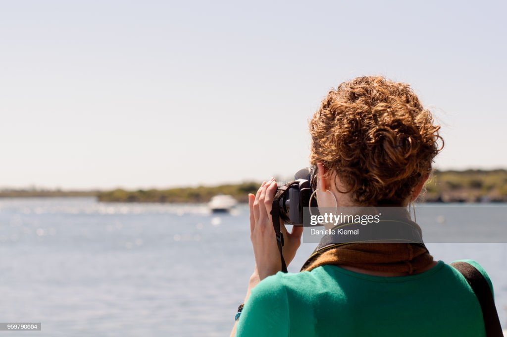 Young woman taking photo of lake : Stock-Foto