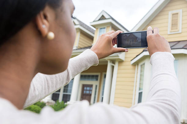 young woman taking photo of new home with smart phone - 攝影 個照片及圖片檔