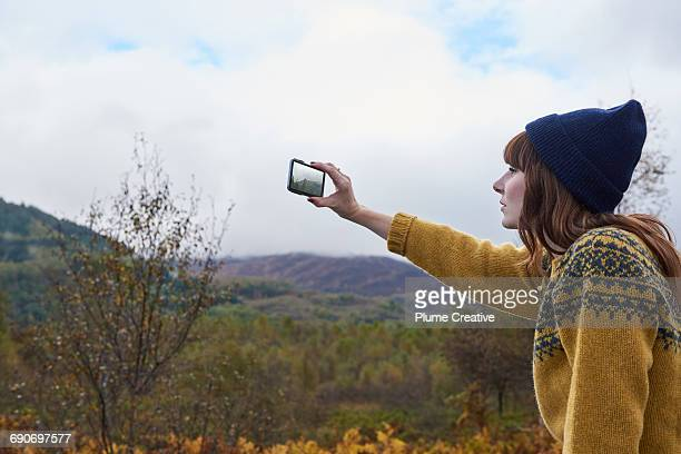 Young woman taking photo of the landscape