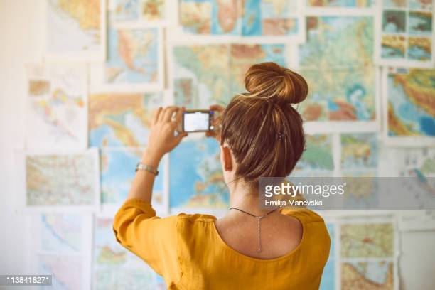 Young woman taking photo with mobile phone and looking at world map