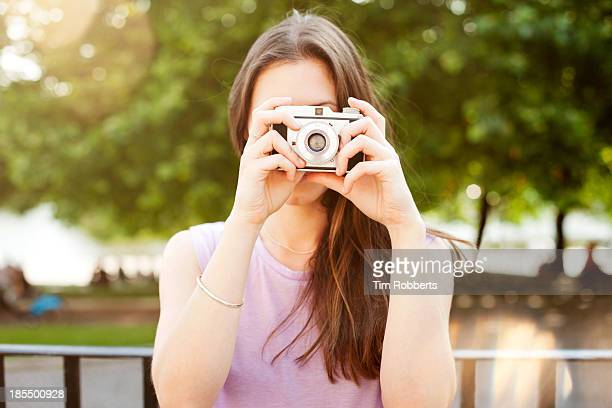 Young woman taking photo with retro camera.