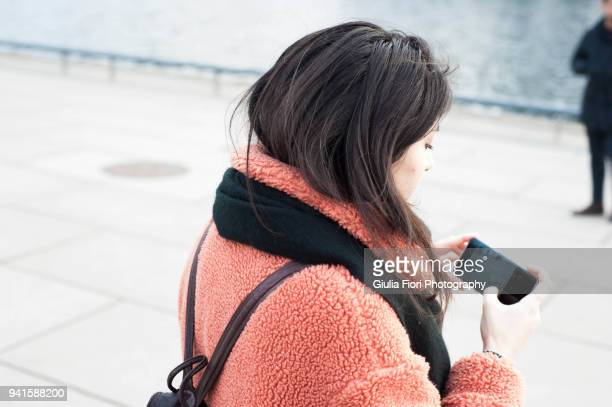 Young woman taking photo with smartphone