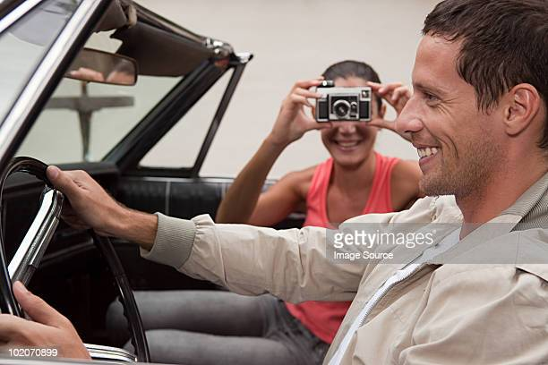 Young woman taking photograph of man in convertible car