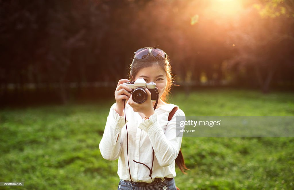 Young woman taking photograph with camera against sunset : Foto stock
