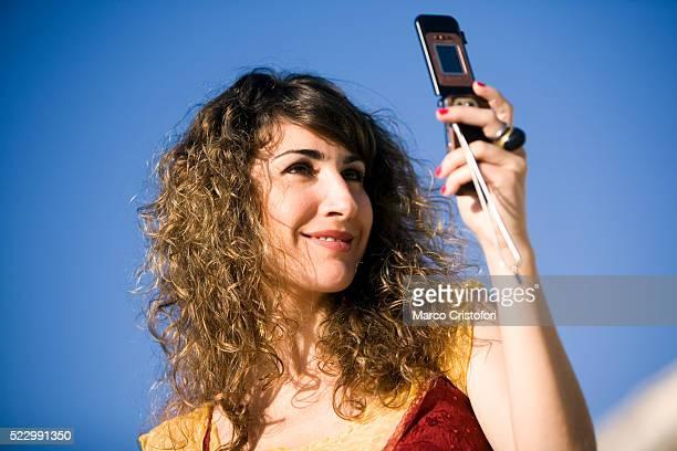 young woman taking photograph with camera phone - marco cristofori fotografías e imágenes de stock