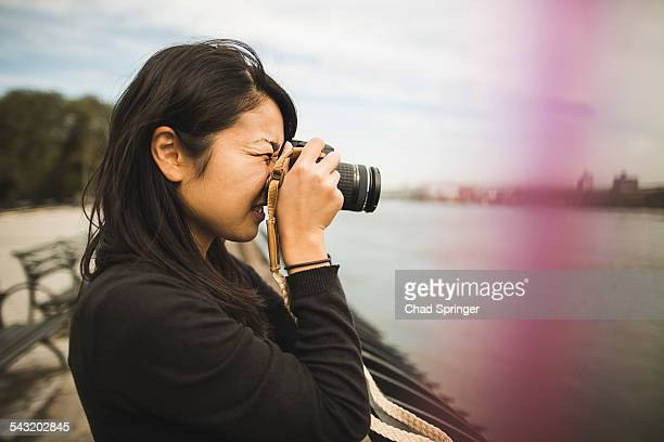 Young woman taking photographs, outdoors